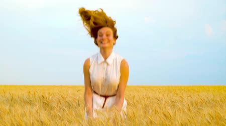 positive vibes : beautiful woman smiling at camera, hiding in wheat field and then jumping up