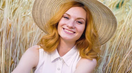 vibes : portrait of young red haired woman in straw hat smiling at camera in wheat field Stock Footage