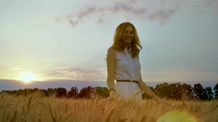 mindset : following shot of pretty woman in wheat field with sun setting on background