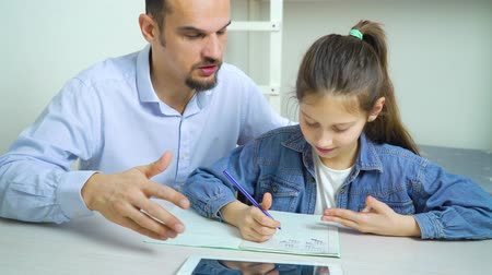 репетитор : private tutor helping little school girl with studies