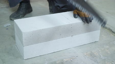 aerated : construction worker sawing aerated concrete block after measuring it