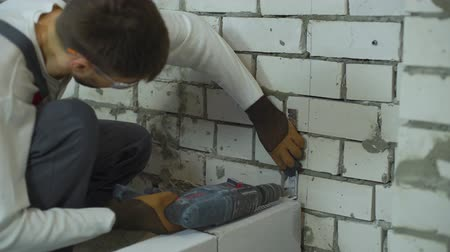 зажим : builder making holes in brick wall with electric drill to fix joining clamp