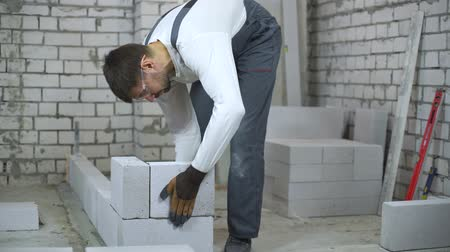 клейкий : builder laying aerated concrete block and checking it with bubble level Стоковые видеозаписи