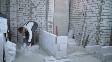 aerated : builder sawing aerated concrete block with hand saw to make it fit the wall gap