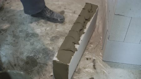 aerated : high angle shot of builder hands in gloves put mixturer on block sides