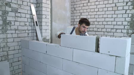 bricoleur : bearded builder in work wear and protective glasses laying blocks