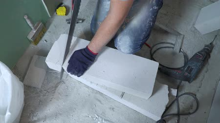 aerated : upper view of builder hands sawing block with hand saw according to marking