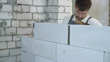 aerated : young builder in protective glasses laying block at construction site Stock Footage
