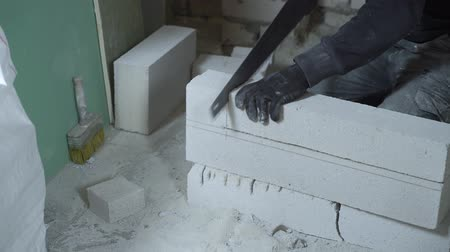 aerated : view of male builder hands sawing block with hand saw according to marking Stock Footage