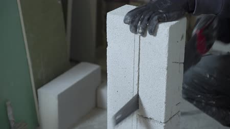 aerated : cropped shot of builde sawing block with hand saw according to marking