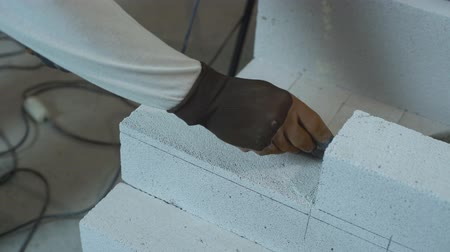 aerated : builder hands marking aerated concrete block with pencil and steel armature bar Stock Footage