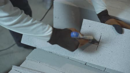 aerated : view of builder hands remove excessive parts of block with construction spatula