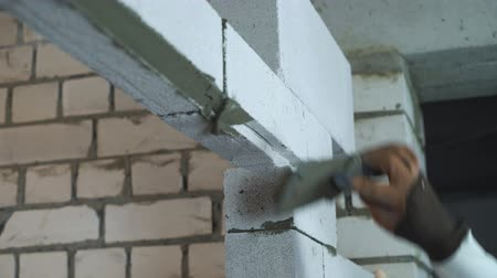 aerated : view of builder hand in glove putting adhesive mixturer on blocks at doorway