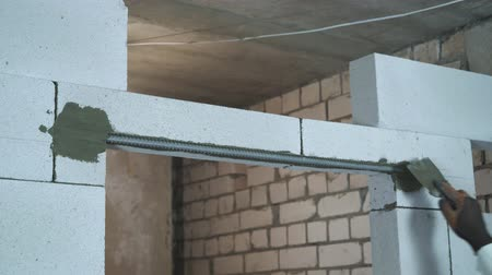 aerated : view of builder hand putting mortar over reinforcement steel bar at doorway