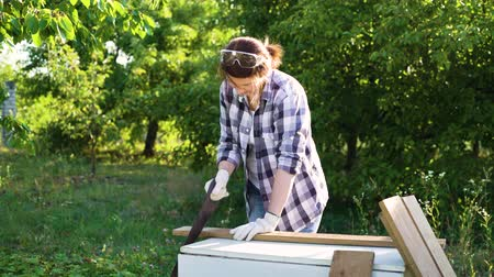 do it yourself : pretty woman carpenter handsawing wooden plank in sunshine in garden
