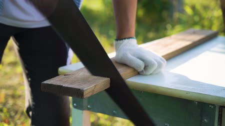 do it yourself : closeup woodworker in working gloves handsawing wooden plank in sunny backyard Stock Footage