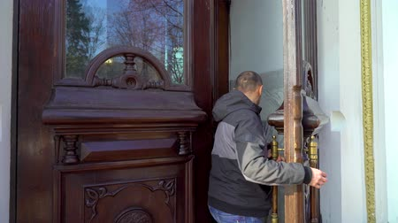 kapualj : adult man opening massive wooden door with embellishment and entering building