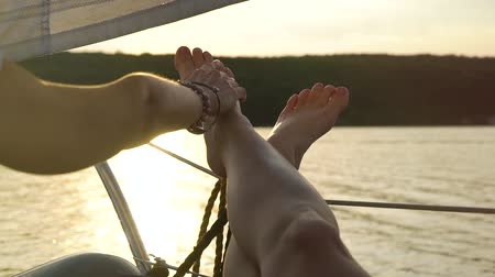 patting : cropped shot of lesbian stroking crossed feet of her partner on sailboat