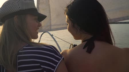 patting : back view of lesbian couple hugging on sailboat floating on river at sunset