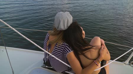 patting : back view of young lesbian family enjoying sunset on sailboat
