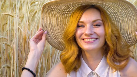 femininity : beautiful red haired woman in big straw hat smiling at camera in wheat field