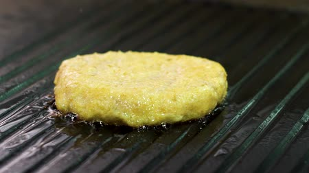 borrifar : closeup of oily sprinkles and steam coming from chicken burger on grill