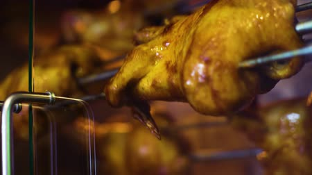 heat resistant : closeup of juicy chicken rotating slowly behind rotisserie glass Stock Footage