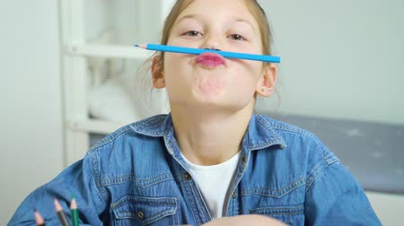 bigode : funny girl looking at camera and making faces with colored pencils as moustache Stock Footage