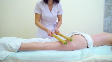 massager : female masseur doing massage with bamboo sticks on woman buttocks and thighs