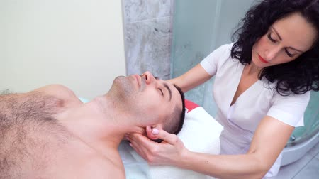 borotválatlan : young beautiful female therapist massaging shoulders and neck of male patient