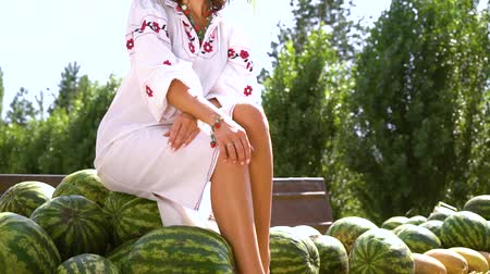 пьедестал : Girl in folk dress posing on watermelons in rural landscape Стоковые видеозаписи
