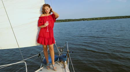 bağımlı : Woman in red dress standing on sailing boat with wine glass Stok Video