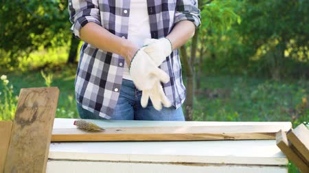 do it yourself : cropped shot of crafts woman putting on protective gloves before woodwork