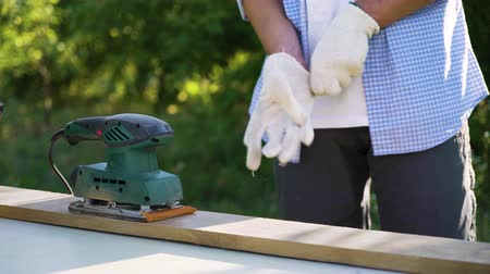 sander : cropped shot of carpenter putting on working gloves and sanding wooden plank Stock Footage