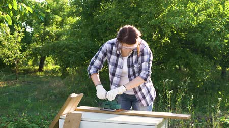 do it yourself : pretty woman carpenter puts on protective glasses and polishes plank with sander
