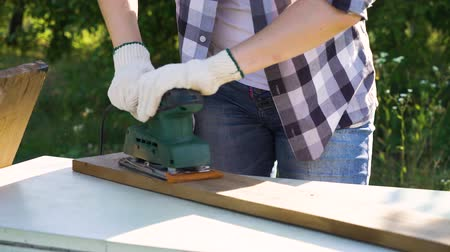 sander : cropped shot of woman in protective gloves polishing plank with electric sander