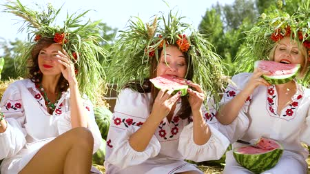 фольклор : Women in ethnic costumes eating watermelons outside