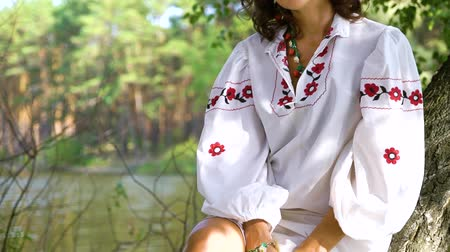 пьедестал : Attractive woman in ethnic ukrainian dress sitting on birch tree near river