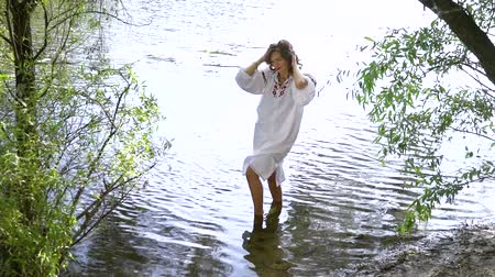 costumes : Girl in ethnic dress standing in river and touching her hair Stock Footage