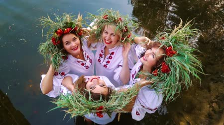 стенд : Four women in floral circlets standing in water