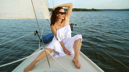 voyager : Young woman in white dress relaxing on sailing boat Stock Footage
