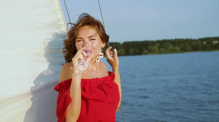 red wine : Beautiful woman smiling at camera and relaxing on sailing boat