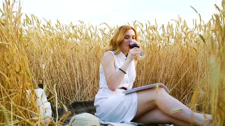 рыжеволосый : Pretty red haired girl having picnic with wine in wheat field