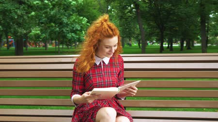 jovial : Cute red haired girl reading funny book in park Vídeos