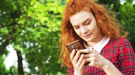 jovial : Happy cute girl with red hair typing message on smartphone sitting in park Vídeos