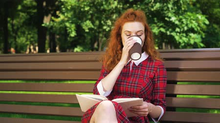 jovial : Amiable red haired reader relaxing in park Vídeos
