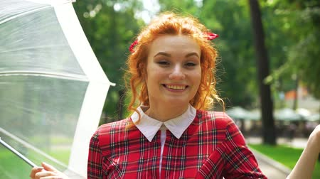 saçlı : Joyful red haired girl walking in sunny park with umbrella Stok Video
