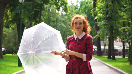 keyifli : Positive girl playing with umbrella in sunny park Stok Video