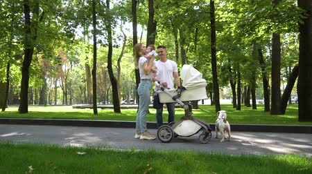терьер : Lovely family with sweet little baby and pet in park