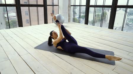 arco : Fitness girl doing scissors exercises in studio with big windows Filmati Stock